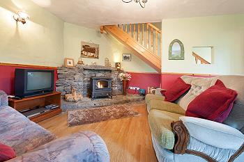 The comfortable sitting area with TV and solid fuel stove